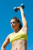 Woman stretching with dumbbell — Stok fotoğraf