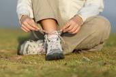 Hiker woman tying shoelaces of boots — Stock Photo