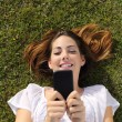Top view of a woman lying on the grass texting on a smart phone — Stock Photo #52537215
