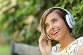 Girl listening to the music with headphones in a park — Stock Photo