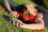 Dziewczyna słuchanie muzyki w słuchawkach i trzyma pewien silny telefon leżąc na trawie — Zdjęcie stockowe
