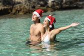 Couple bathing on the beach on christmas holidays — Stock Photo