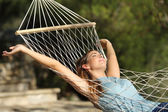 Happy woman relaxing on a hammock on holidays and raising arms — Stockfoto