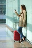 Traveler woman using a smart phone and waiting in an airport — Stock fotografie