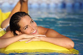 Girl enjoying summer vacations on a mattress in a pool and looking at side — Stockfoto