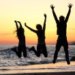 Friends silhouette jumping happy on the beach at sunset — Stock Photo #64410539
