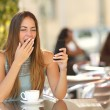 Woman yawning while is working at breakfast in a restaurant — Stock Photo #64748369