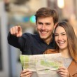 Couple of tourists searching a street in a map — Stock Photo #64827485