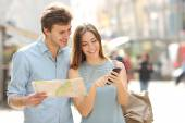 Couple of tourists consulting a city guide and smartphone gps — Stock Photo