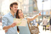 Couple of tourists consulting a city guide searching locations — Stock Photo
