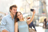 Couple of tourists photographing a selfie in a city street — Stock Photo