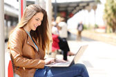 Girl using a laptop while waiting in a train station — Stock Photo
