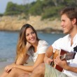 Man flirting playing guitar while a girl looks him amazed — Stock Photo #74338749