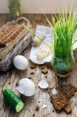 Hard boiled eggs, cucumber, camembert cheese, germinated seeds of grass and wholegrain crisps on the vintage wooden table — Stock Photo