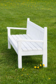 White wooden bench on green grass in park — Stock Photo