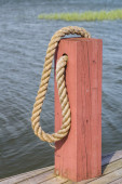 Red wooden boat bollard and rope — Stock Photo