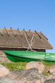 Fisherman rowboat and old rustic utility house — Stock Photo