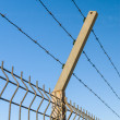 Security barbed wire fence against blue sky — Stock Photo #75087329