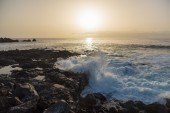 Sun setting over waves breaking on seacoast of Tenerife island — Stock Photo