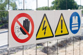 Warning signs on fence at construction site — Stock Photo
