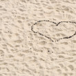 Heart of conifer cones inlaid on a background of sand — Stock Photo #78689540
