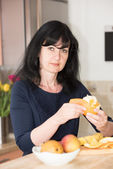 Woman in the kitchen with an orange — Stock Photo
