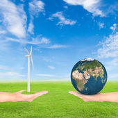 Hand holding wind turbine and earth — Stock Photo