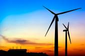 Silhouette wind turbine generator with factory emissions of carb — Stock Photo