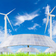 Solar panels and wind turbine on green grass field against blue — Stock Photo #57243305