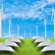 Solar panels and wind turbine on green grass field against blue — Stock Photo #57243459