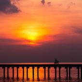 Мальчик силуэта ездит на велосипеде на мосту на закате — Стоковое фото