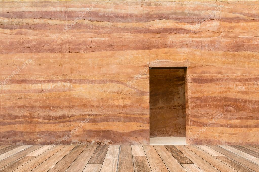 Parete di pietra con porta e pavimento di legno nella parte ...