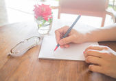 Writing love letter on romantic table — Stock Photo