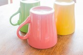 Colorful ceramic cups on wooden table — Stock Photo
