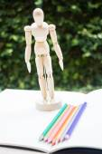 Wood mannequin standing on artist drawing paperbook — Stock Photo