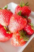 Fresh ripe strawberries on white plate — Stock Photo