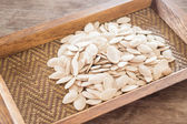 Pumpkin seeds on wooden tray — Stock Photo