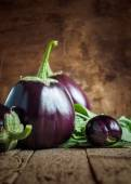 Dark Round Eggplants on the wooden background — Stock Photo