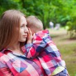 Young Mother Holds Her Son on Hands in the Summer Park — Stock Photo #78216800