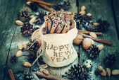 Cinnamon in Bag with Embroidery Happy New Year and  other christmas ingredients. Toned — Stock Photo