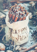 Sticks of Cinnamon in a linen Bag Embroidered with Happy New Year — Stock Photo