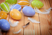 Easter eggs and plumelets on wooden background — Stock Photo