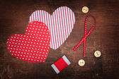 Textile hearts and buttons on old shabby wooden background — Stock fotografie
