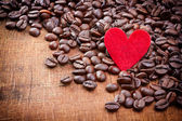 Red heart and Coffee beans on wood background — Stock Photo