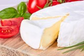 Goat cheese, cherry tomato, and basil on a wooden board — Стоковое фото