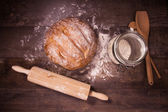 Fresh baked bread covered with flour on a wooden table — Stock Photo