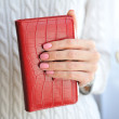 Bright red notebook in a beautiful female hand — Stock Photo #71644531