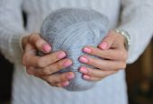 Skein of thread in female hands — Stock Photo