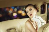 Beautiful and rich superstar girl sitting in a retro car — Stock Photo
