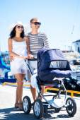 Attractive couple walking with baby pram — Stock Photo